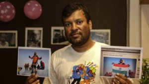 "Satyarup Sidhantha holds the genuine photo in his right hand and the ""doctored"" photo in his left hand [AP]"